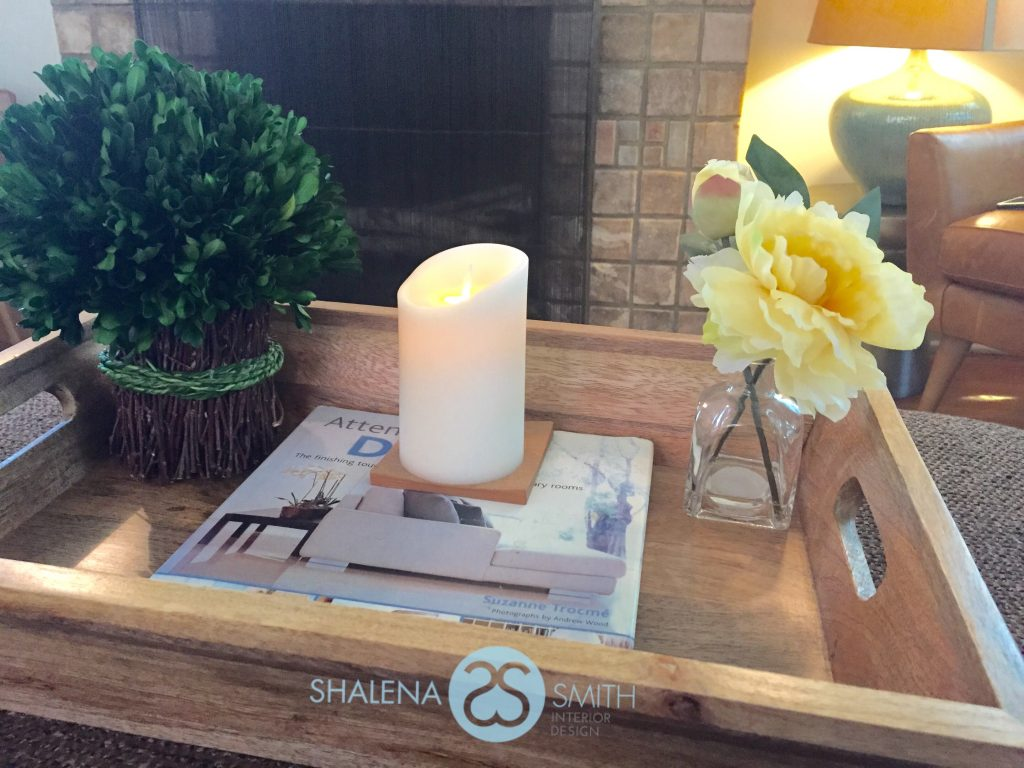 Purchase a serving tray and decorate it for your coffee table or ottoman.